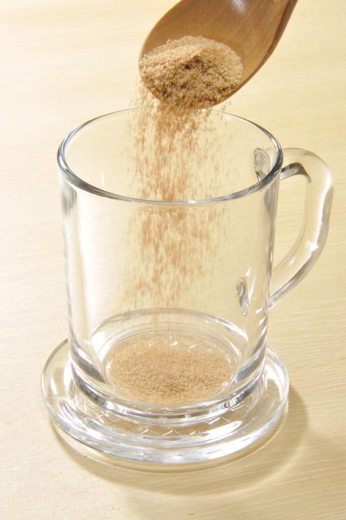 スプーン一杯の顆粒をグラスに入れ、